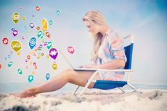 Composite image of pretty blonde sitting on beach using her laptop Royalty Free Stock Photography
