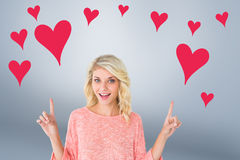 Composite image of pretty blonde smiling and pointing up Stock Photos