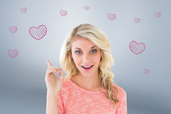 Composite image of pretty blonde smiling and pointing up Stock Photo
