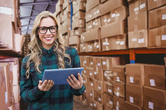 Composite image of pretty blonde with tablet. Pretty blonde with tablet against forklift in large warehouse Royalty Free Stock Photos