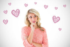 Composite image of pretty blonde thinking with hand on chin Royalty Free Stock Photography