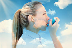 Composite image of pretty blonde using an asthma inhaler Royalty Free Stock Photo