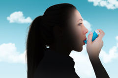 Composite image of pretty blonde using an asthma inhaler Royalty Free Stock Photography