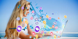 Composite image of pretty blonde using her laptop at the beach Royalty Free Stock Image