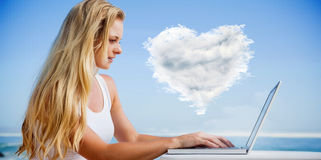 Composite image of pretty blonde using her laptop at the beach Stock Images