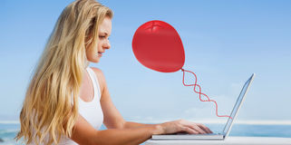 Composite image of pretty blonde using her laptop at the beach Stock Photo