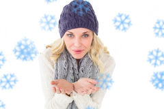 Composite image of pretty blonde in winter fashion blowing over hands Stock Photo