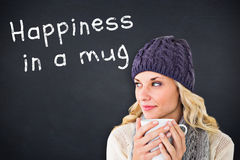 Composite image of pretty blonde in winter fashion holding mug Royalty Free Stock Photos