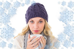 Composite image of pretty blonde in winter fashion holding mug Stock Image