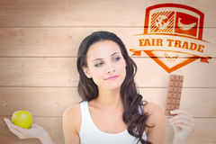 Composite image of pretty brunette deciding between apple and chocolate Stock Image