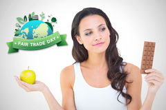 Composite image of pretty brunette deciding between apple and chocolate Royalty Free Stock Images
