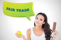 Composite image of pretty brunette deciding between apple and chocolate Stock Images