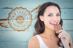 Composite image of pretty brunette eating bar of chocolate Stock Photos