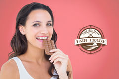 Composite image of pretty brunette eating bar of chocolate Royalty Free Stock Image