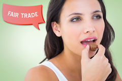 Composite image of pretty brunette eating chocolate candy Royalty Free Stock Image