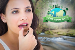 Composite image of pretty brunette eating chocolate candy Stock Photo
