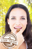 Composite image of pretty brunette eating chocolate candy Stock Photos