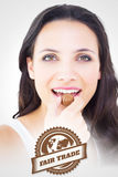 Composite image of pretty brunette eating chocolate candy Royalty Free Stock Images