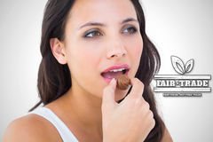Composite image of pretty brunette eating chocolate candy Royalty Free Stock Photography