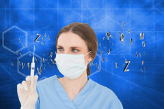Composite image of pretty brunette female doctor holding a syringe and looking at it Royalty Free Stock Images