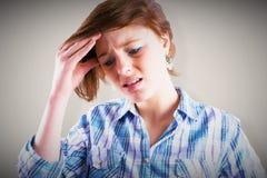 Composite image of pretty brunette getting a headache Stock Photo
