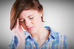 Composite image of pretty brunette getting a headache Stock Images