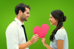 Composite image of pretty brunette giving boyfriend her heart Royalty Free Stock Photo