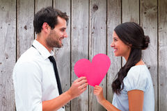 Composite image of pretty brunette giving boyfriend her heart Stock Photography