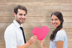 Composite image of pretty brunette giving boyfriend her heart Stock Image