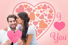 Composite image of pretty brunette giving boyfriend a kiss and her heart Stock Photos