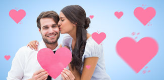 Composite image of pretty brunette giving boyfriend a kiss and her heart Stock Photo