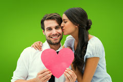 Composite image of pretty brunette giving boyfriend a kiss and her heart Royalty Free Stock Image