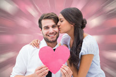 Composite image of pretty brunette giving boyfriend a kiss and her heart Royalty Free Stock Photos
