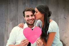 Composite image of pretty brunette giving boyfriend a kiss and her heart Royalty Free Stock Photography
