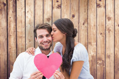 Composite image of pretty brunette giving boyfriend a kiss and her heart Royalty Free Stock Photo