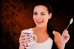 Composite image of pretty brunette having cup of tea Royalty Free Stock Photography
