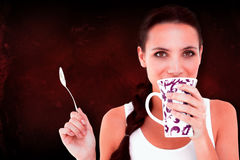 Composite image of pretty brunette having cup of tea Stock Photography