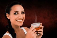 Composite image of pretty brunette having cup of tea Stock Image
