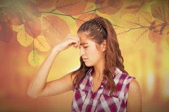 Composite image of a pretty brunette with headache Royalty Free Stock Photo