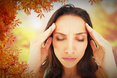 Composite image of pretty brunette with a headache Royalty Free Stock Photos