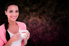 Composite image of pretty brunette holding a mug Royalty Free Stock Images