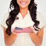 Composite image of pretty brunette holding out hands. Pretty brunette holding out hands against usa national flag Royalty Free Stock Images