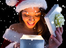 Composite image of pretty brunette in santa outfit opening gift Stock Photos