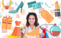 Composite image of pretty brunette with shopping bags. Pretty brunette with shopping bags against digital image of shopping doodles Royalty Free Stock Image