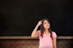 Composite image of pretty brunette thinking Royalty Free Stock Image