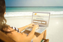 Composite image of pretty brunette using laptop on deck chair Royalty Free Stock Photo