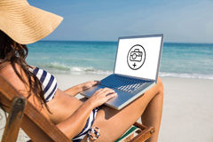 Composite image of pretty brunette using laptop on deck chair Stock Photo