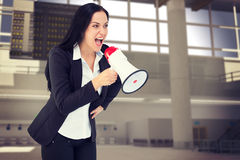 Composite image of pretty businesswoman shouting with megaphone Royalty Free Stock Photography