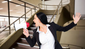 Composite image of pretty businesswoman shouting with megaphone Stock Photo