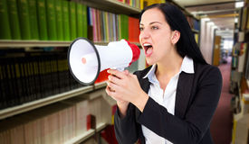 Composite image of pretty businesswoman shouting with megaphone Royalty Free Stock Photo